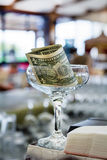 Glass with one dollar banknote.Tip. Glass with one dollar banknote .Gratuity royalty free stock photo