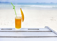 Glass of orange colour juice on the beach Royalty Free Stock Photos