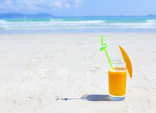 Glass of orange colour juice and sand and sea Stock Photo