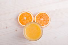 Glass of orange fresh juice on a light table and orange ears top Stock Images