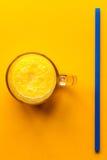 Glass with orange fresh juice and straw. Glass with raw orange fresh juice and straw on orange table Stock Photo