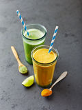 Glass of orange and green smoothie Stock Photos