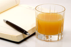 A glass orange juice. With a business diary Royalty Free Stock Photo