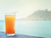 Glass of orange juice on the background of the sea Stock Photo