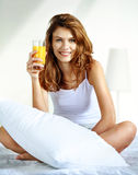 Glass of orange juice in bed Stock Photography