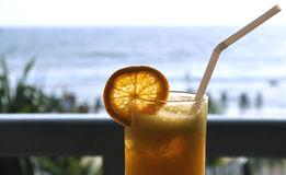 A glass of orange juice at a cafe by the beach Royalty Free Stock Photo
