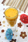A glass of orange juice on colorful background. A glass of orange juice with paper umbrella on colorful background Royalty Free Stock Image
