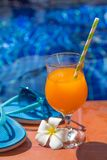 Glass of orange juice drink fresh with flowers, sunglasses and s Stock Photography