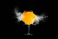 Glass with orange juice explosions. At the black background royalty free stock photo