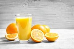 Glass of orange juice and fresh fruits. On table Stock Image