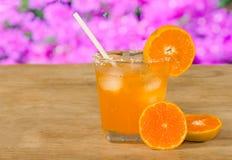 Glass of orange juice and fresh orange  on wooden table Stock Images