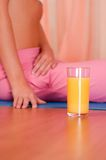 Glass of orange juice in front of sporty woman Royalty Free Stock Photos