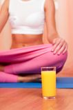 Glass of orange juice in front of sporty woman Stock Photography