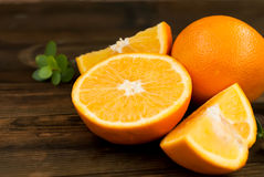 Glass of orange juice and a group of oranges on dark board Stock Photo