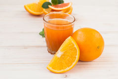 Glass of orange juice and a group of oranges on white board yabl Royalty Free Stock Photography