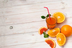 Glass of orange juice and a group of oranges on white board yabl Royalty Free Stock Photos