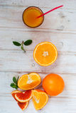 Glass of orange juice and a group of oranges on white board yabl Royalty Free Stock Images