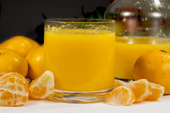 Glass of orange juice beside a jar and several fruits Royalty Free Stock Photos