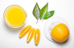 Glass of orange juice, a juicer, slices with leaves Royalty Free Stock Photo