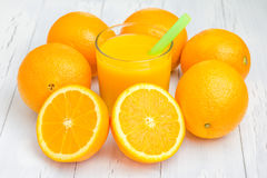Glass of orange juice and oranges. On white table Royalty Free Stock Photo