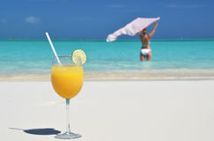 Glass of orange juice on the sandy beach Royalty Free Stock Photography