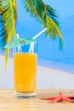 Glass of orange juice on the sandy beach near starfish Royalty Free Stock Photography