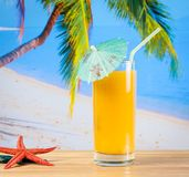 Glass of orange juice on the sandy beach near starfish Royalty Free Stock Images