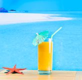 Glass of orange juice on the sandy beach Stock Images