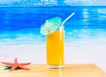 Glass of orange juice on the sandy beach Stock Image