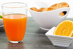 A glass of orange juice with a sliced orange fruit in a bowl on Royalty Free Stock Photography