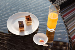 Glass of orange juice and snack on rattan table Royalty Free Stock Images