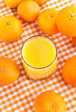 Glass of orange juice with some tangerines. Around Royalty Free Stock Photos