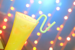 A glass of orange juice with straw on natural out of focus background Stock Photography