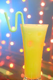 A glass of orange juice with straw on natural out of focus background Royalty Free Stock Images