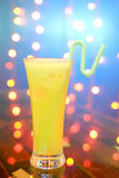 A glass of orange juice with straw on natural out of focus background Stock Image