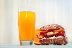 Orange juice and stuffed bun-Chrono diet. Glass of orange juice and stuffed bun with orange in the background-Chrono diet Stock Images