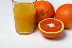 A glass of orange juice on the white background stands next to two whole oranges and sliced red orange stock photo