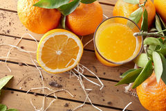 Glass of orange juice on a wooden table top. Glass of orange juice on a wooden table with oranges and orange sections. Horizontal composition. Top view Stock Photography