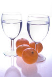 Glass and oranges. Glasses of water with oranges on reflective surface Stock Images
