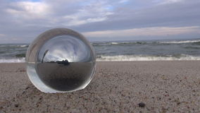 Glass orb by the sea with waves crashing on shore. Glass orb with reflection of man by the sea with waves crashing on shore on overcast day stock video