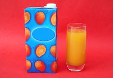Glass and pack of cold mango juice drink. Royalty Free Stock Photo