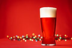 Glass of of pale lager beer or ale with big head of foam and christmas lights on red background royalty free stock photos