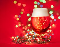 Glass of pale lager beer or ale with christmas lights on red background royalty free stock image