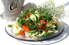 Glass palte with green salad. Glass plate with green salad and oil canister, flowers and garlic on the back Stock Image