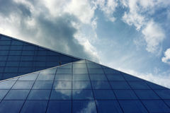 The glass panels of a building with reflection of clouds Stock Image