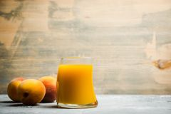 Glass of peach juice with fresh peaches on the rustic background Stock Photography
