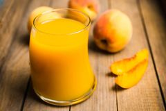 Glass of peach juice with fresh peaches on the rustic background Royalty Free Stock Photo