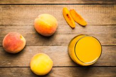 Glass of peach juice with fresh peaches on the rustic background Stock Image