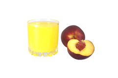 Glass of peach juice and peaches on a white background. Yellow peach juice in a glass near peaches on the white, isolated background Stock Photos