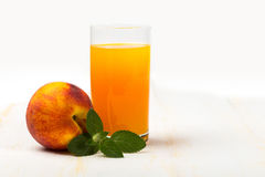 Glass with peach juice and ripe peach and green mint Stock Photos